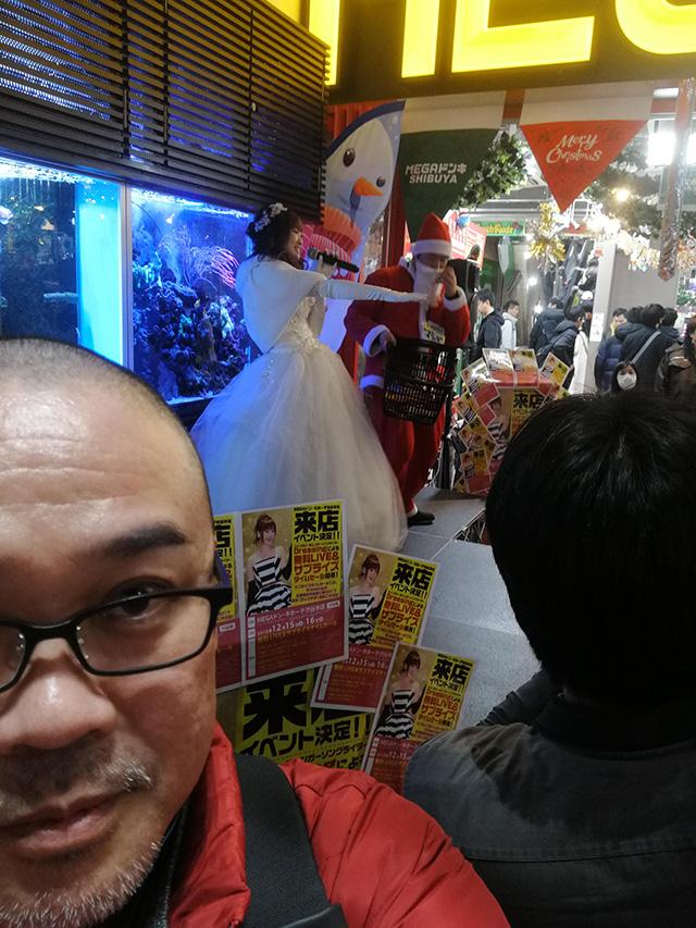アップリンク渋谷への道中、メガドン・キホーテ渋谷本店店頭の熱帯魚の前ではファンタジー系シンガーソングライター Dressing ライブ